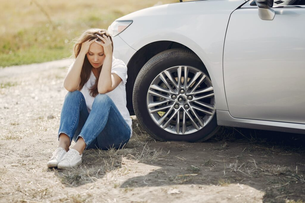 Worried young woman sitting near broken automobile at roadside in countryside