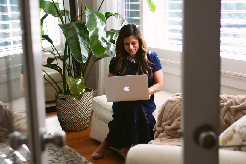 Mona working with a laptop sitting by the window