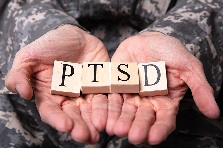 Male Soldier Holding Wooden Cubes With PTSD Text